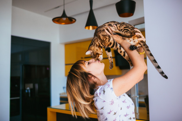 woman holds cat up in the air
