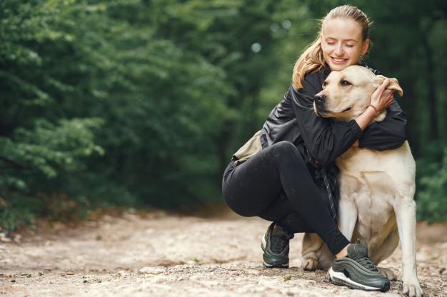 woman cuddling dog outside